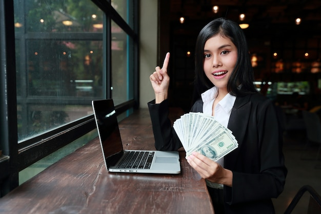 Empresária mostrando dinheiro nas mãos com o computador na mesa.