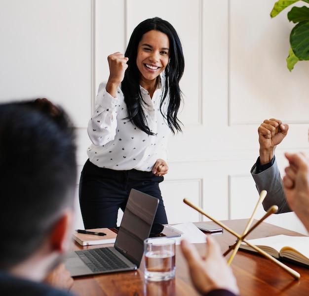 Empresária motivando os membros da equipe em uma reunião