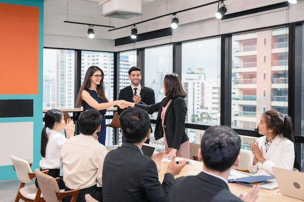 Empresária multiétnica cumprimentando cooperação para acordo corporativo com colegas de trabalho em um escritório moderno