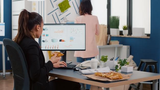 Empresária na hora do almoço, sentada à mesa, comendo fastfood delivery no escritório da empresa