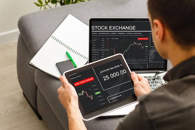 Empresária negociando ações com tablet e gráfico de análise no computador desktop