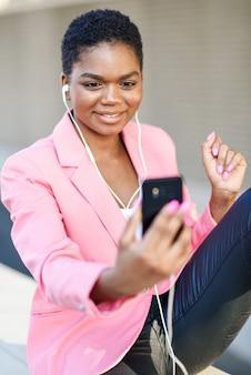 Empresária negra sentada ao ar livre, falando por videoconferência com seu smartphone.