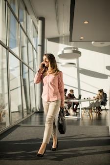 Empresária no celular andando no escritório
