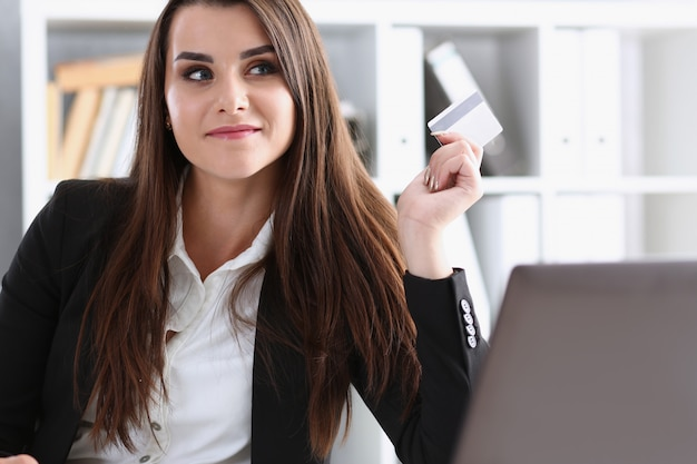 Empresária no escritório tem um cartão de débito plástico na mão, faz compras on-line e comércio de conteúdo na loja virtual na internet