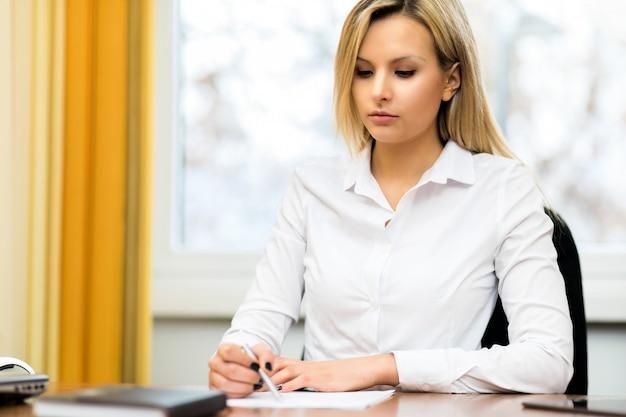 Empresária ocupada, escrevendo em uma agenda em uma área de trabalho no escritório