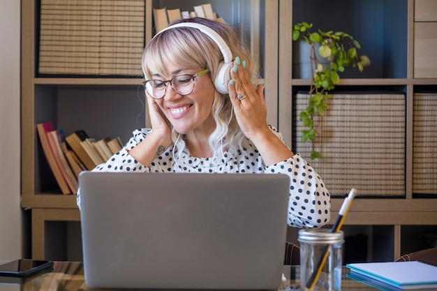 Empresária ouvindo música em fones de ouvido enquanto trabalhava no laptop no escritório em casa. mulher jovem caucasiana, curtindo música em fones de ouvido. mulher alegre com laptop e fones de ouvido no escritório em casa