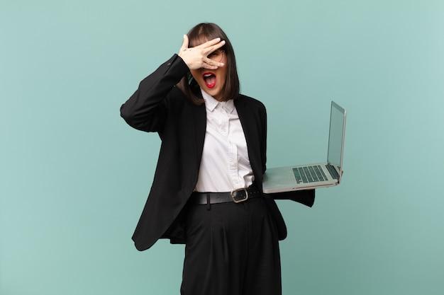 Empresária parecendo chocada, assustada ou apavorada, cobrindo o rosto com a mão e espiando por entre os dedos