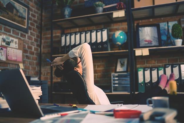 Empresária pensando no escritório ela relaxar