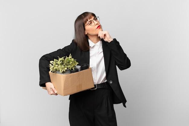 Empresária pensando, sentindo-se duvidosa e confusa, com opções diferentes, imaginando qual decisão tomar