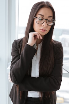 Empresária pensativa em pé e pensando perto da janela no escritório