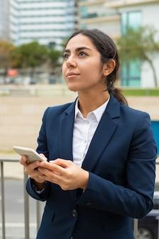 Empresária pensativa usando smartphone