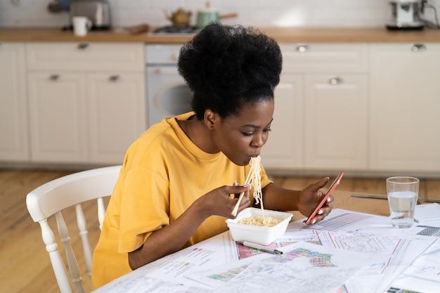 Empresária remota com pressa, comer e conversar no smartphone, sentar na mesa da cozinha com a planta do projeto