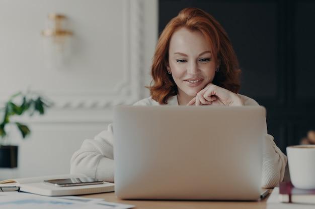 Empresária ruiva experiente lê publicação no computador portátil moderno