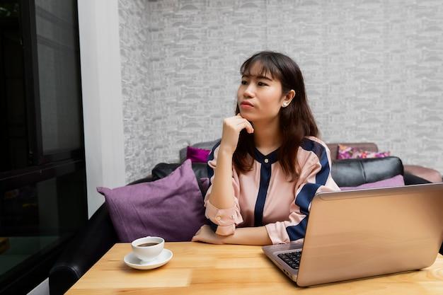 Empresária se sentou na frente do laptop e olhou pela janela.