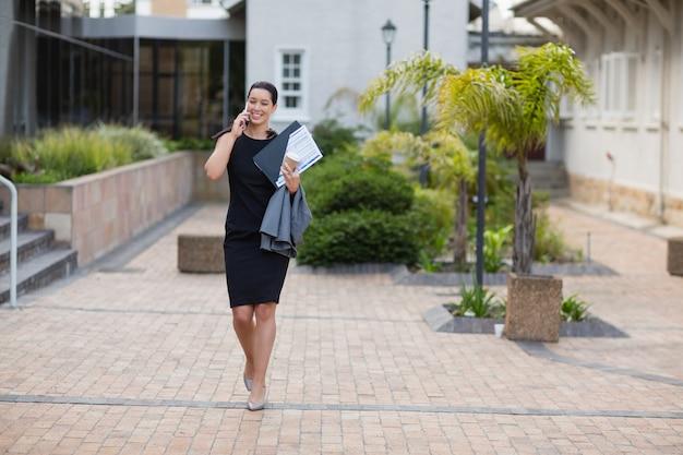 Empresária, segurando a área de transferência e falando no celular