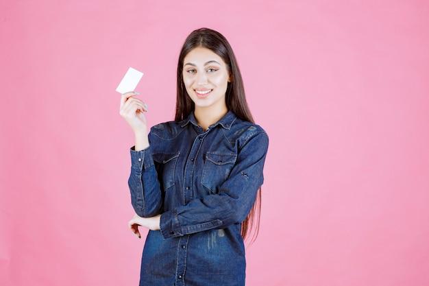 Empresária segurando e apresentando seu novo cartão de visita