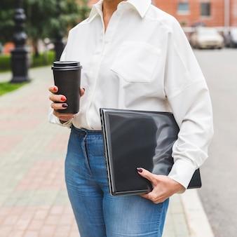 Empresária segurando laptop e café
