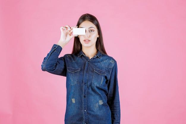 Empresária segurando o cartão de visita contra o olho