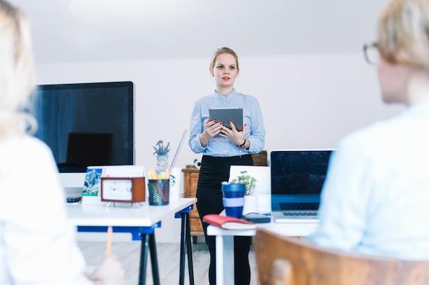 Empresária segurando o tablet digital? na mão dando apresentação aos colegas no escritório