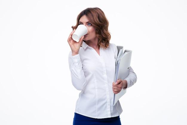 Empresária segurando pastas e bebendo café