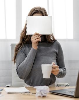 Empresária segurando um bloco de notas em branco no rosto