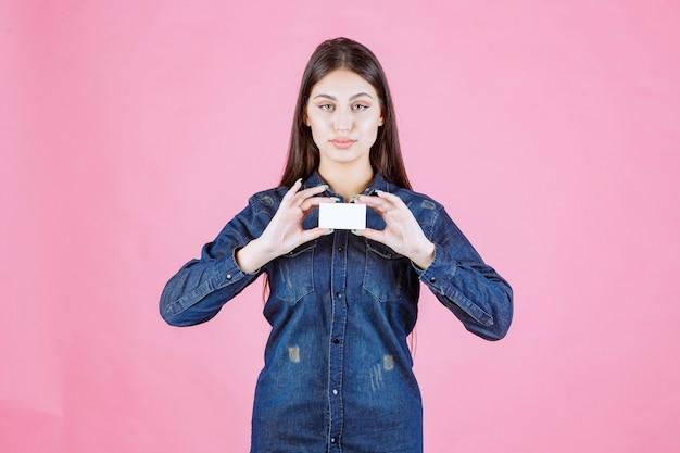 Empresária segurando um cartão de visita com as duas mãos