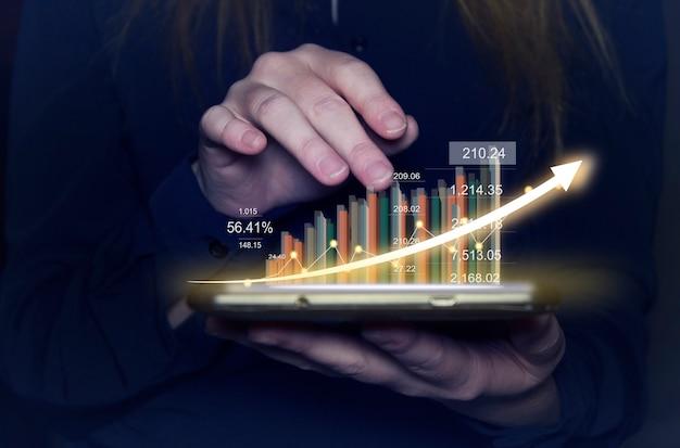 Empresária segurando um tablet e mostrando um holograma virtual crescente do gráfico de estatísticas