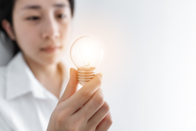 Empresária segurando uma lâmpada acesa, em fundo branco