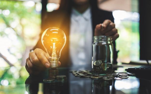 Empresária, segurando uma lâmpada sobre a pilha de moedas em cima da mesa enquanto coloca a moeda em uma jarra de vidro para economizar energia e dinheiro conceito