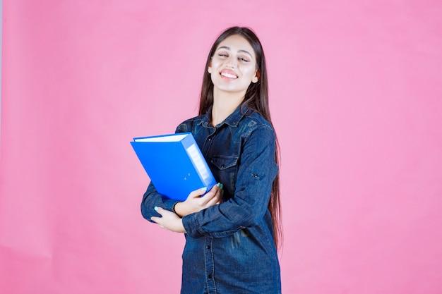 Empresária segurando uma pasta azul com autoconfiança