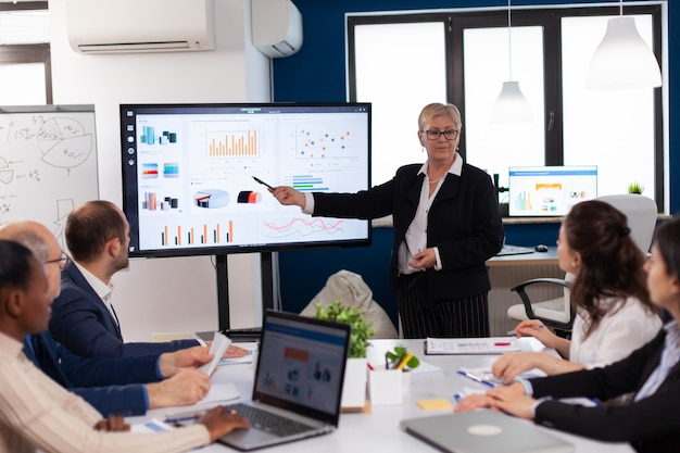 Empresária sênior de inicialização segurando uma apresentação na sala de conferências com informações do gráfico