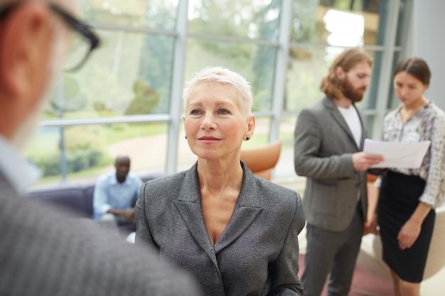 Empresária sênior falando com parceiro