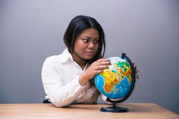 Empresária sentada à mesa com globo