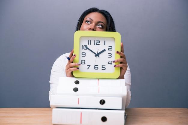 Empresária sentada à mesa com relógio