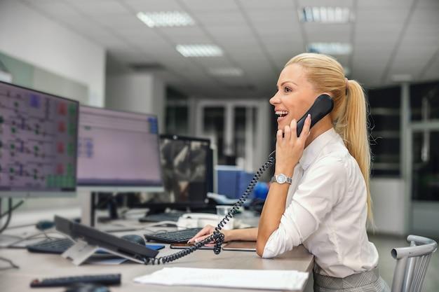 Empresária, sentada na sala de controle em uma planta de aquecimento e conversando ao telefone com seu chefe.