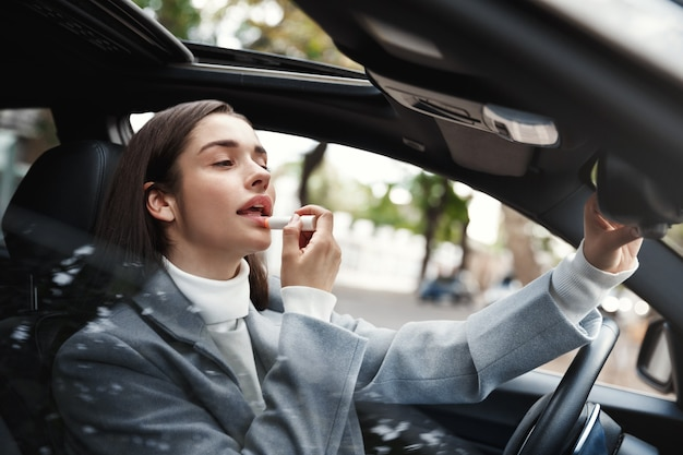 Empresária sentada no carro usando batom, olhando-se no espelho retrovisor para verificar a maquiagem