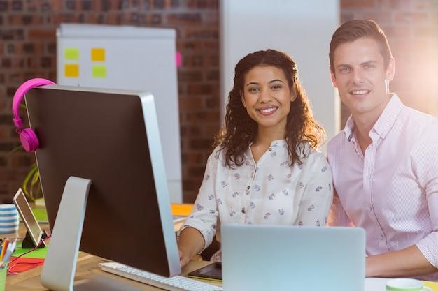 Empresária sentado com colega de trabalho enquanto trabalha no computador