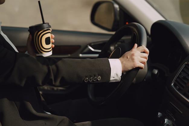 Empresária, sentado dentro de um carro e bebe um café