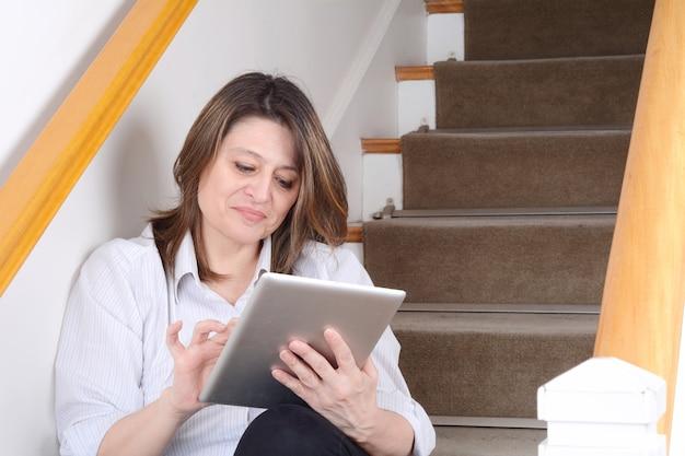 Empresária, sentado na escada usando o tablet.