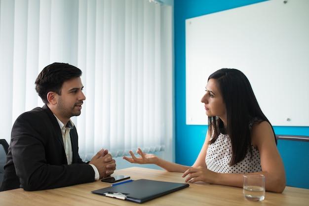 Empresária séria e empresário falando na sala de reuniões