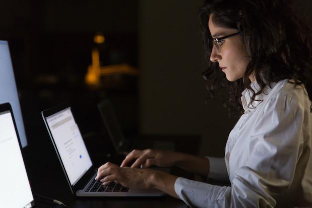 Empresária séria usando laptop no escritório escuro