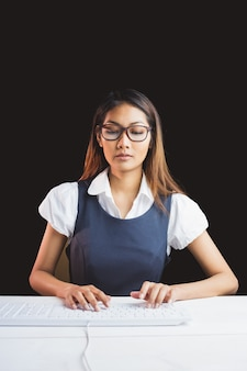 Empresária séria usando um computador em fundo preto
