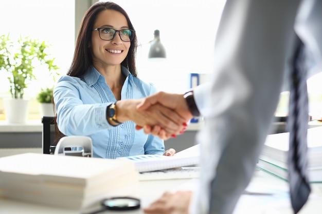 Empresária sorri e agita as mãos com seu parceiro