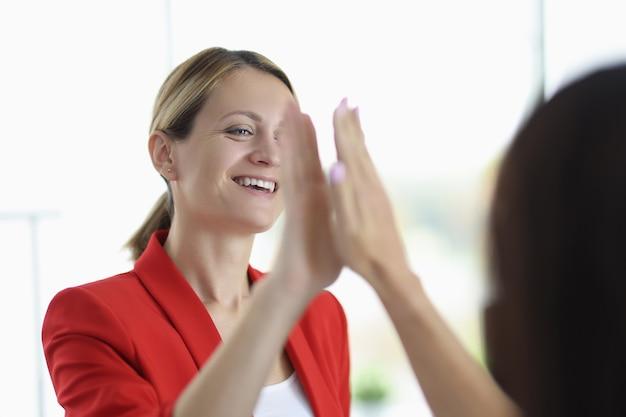 Empresária sorri e dá cinco para o colega
