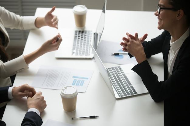 Empresária sorridente, apreciando a conversa com os colegas durante o trabalho em equipe com laptops