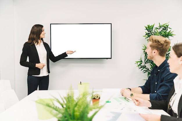 Empresária sorridente confiante, dando a apresentação para seus parceiros
