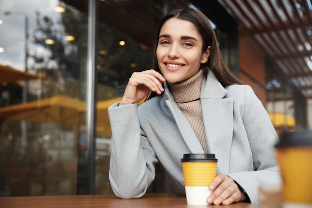 Empresária sorridente descansando em uma cafeteria.