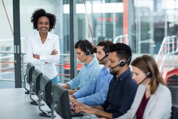 Empresária sorridente em pé com os braços cruzados enquanto colegas falando no fone de ouvido
