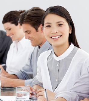Empresária sorridente em uma reunião com seu time