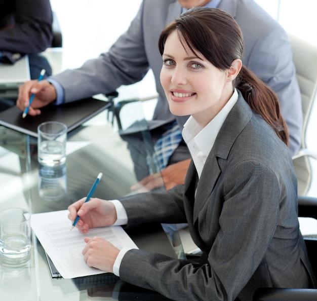 Empresária sorridente estudando um documento em uma reunião